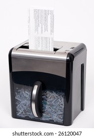 A paper shredder with a confidential document about to be shredded