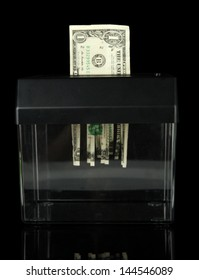 Paper shredder machine with dollar banknote, isolated on black