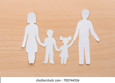 Paper silhouette of family on wooden background. Life insurance concept