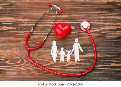 Paper silhouette of family, stethoscope and heart on wooden background. Health insurance concept