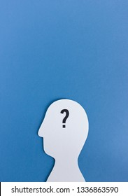 Paper silhouette of human head with black question mark in mind on blue background