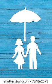 Paper silhouette of man and woman holding hands under umbrella on blue wooden background. Concept of family love