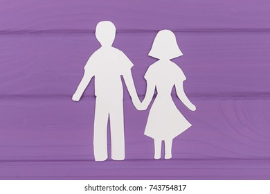 Paper silhouette of man and woman holding hands on purple wooden background. Concept of family love