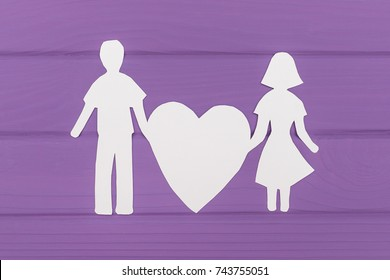 Paper silhouette of man and woman holds big heart on purple wooden background. Concept of family love