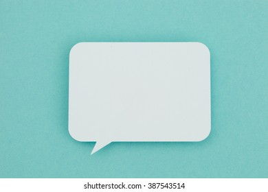 Paper speech bubble on a blue background. Conceptual image about communication and social media.