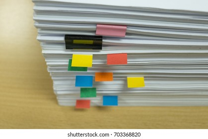 A paper stack with color tag on yellow table top