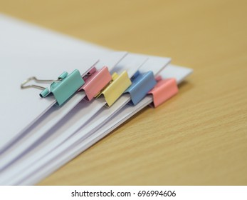Paper stack with colorful binder or clip in pastel color in green pink yellow and pink and place on brown color table