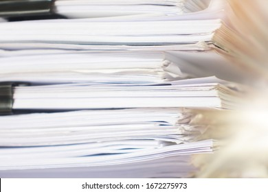 Paper stack on the desk related to business functions.
