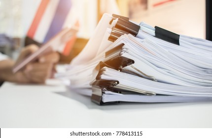 Paper stack, Pile of unfinished documents on office desk related to business functions. Stack of business papers for Annual Report files on blur National flag,use smart phone. Business offices concept