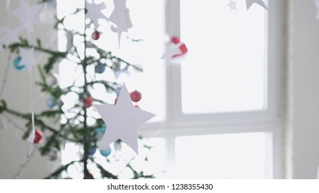 Paper stars hanging for background of a Christmas interior by the fir-tree next to the window. Christmas concept