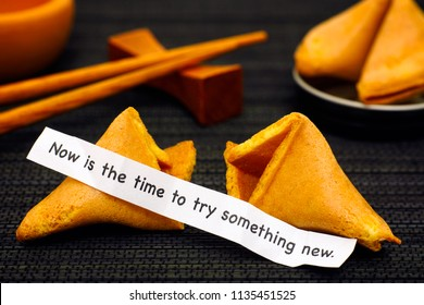 Paper strip with phrase Now is the Time to Try Something New from fortune cookie, another cookie and chopsticks on black napkin background.