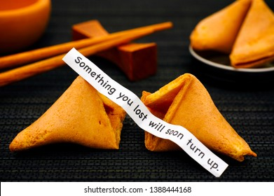 Paper strip with phrase Something You Lost Will Soon Turn up. from fortune cookie, another cookie and chopsticks on black napkin background.