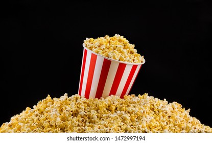 Paper striped bucket installed on scattered popcorn isolated on black background, concept of watching TV or cinema.
