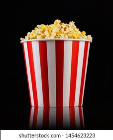 Paper striped bucket with popcorn on isolated black background, concept of watching TV or cinema.