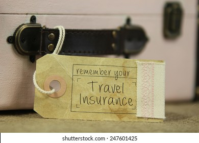 Paper tag with the handwritten words 'remember your travel insurance' on vintage suitcase.