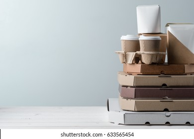 Paper take-out coffee cups in holder, French fries container, pile of pizza boxes, close-up. Grey background, place to insert your text. Emotional eating.