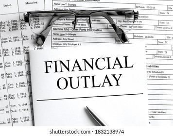 Paper with text Financial Outlay on a financial table with eyeglasses and metal pen. Financial and concept photo