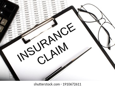 Paper with text INSURANCE CLAIM on table on chart
