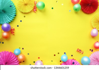 Paper texture flowers with different baloons on yellow background. Birthday, holiday or party background. Flat lay style.