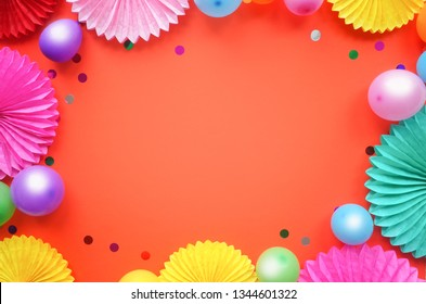 Paper texture flowers with different baloons on orang background. Birthday, holiday or party background. Flat lay style.