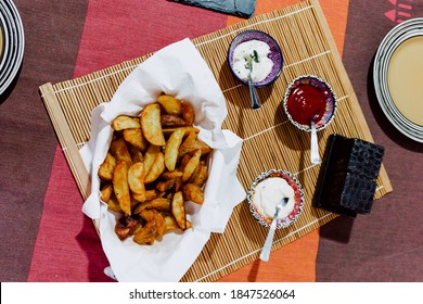 Paper towel basket filled with deluxe potato chips along with 3 containers of different sauces, ketchup, mayonnaise and yoghurt sauce. All on a wooden tablecloth. food photography.