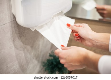 Paper towel dispenser. Hand of woman takes paper towel in bathroom.
