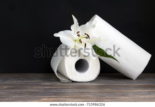 Paper towel rolls - paper tissue on wooden table against black background. Copy space.