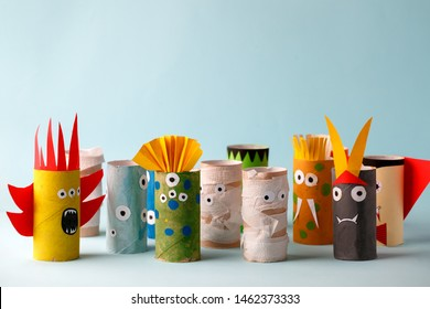 paper toy ghost, bat, monsters for Halloween party. Easy crafts for kids on blue background, copy space, die creative idea from toilet tube, recycle concept