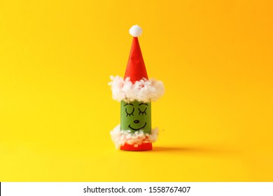 Paper toy grinch for Happy new year Merry Christmas party. Easy crafts for kids on yellow background, simple diy idea from toilet rool tube, recycle concept, copy space