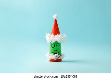 Paper toy grinch for Happy new year Merry Christmas party. Easy crafts for kids on blue background, simple diy idea from toilet rool tube, recycle concept, copy space