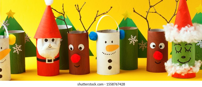 Paper toy santa, snowman, reindeer, grinch, xmas tree for Happy new year Merry Christmas party. Easy crafts for kids on yellow background, idea from toilet rool tube, recycle