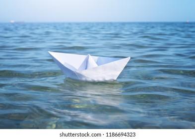 Paper toy ship and deep blue sea. Conceptual design.