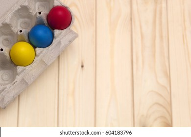 A paper tray with Easter eggs. Wooden background. Easter.