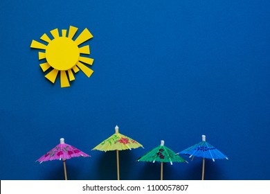 Paper umbrellas under sun. Origami. Sun protection and summer vacation concept