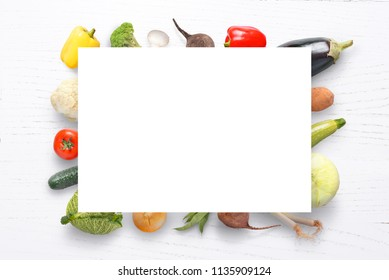 Paper and vegetables on white wooden table. Copyspace. Top view.