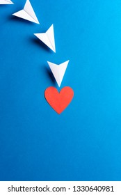 Paper white airplanes with red heart shape with copy space on blue background. Social media, sharing and send concept. Marketing landing page concept.