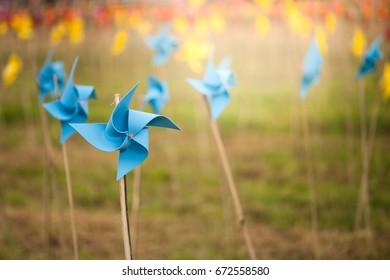 Paper windmills in green grass field