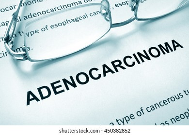 Paper with word adenocarcinoma and glasses.