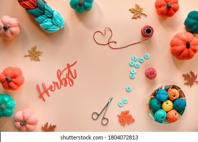 Paper word Herbst means Autumn in German language. Autumn seasonal DIY wool pumpkins, wool bundle, cord and buttons. Hobby craft in designers shades of Fall colors, orange, yellow, red, green. - Shutterstock ID 1804072813