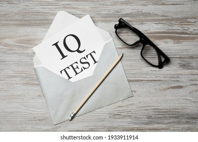 Paper with words IQ Test in envelope, pencil and glasses on wooden table, flat lay