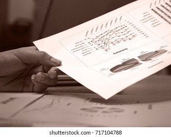 The paper work,investment chart was taking from wooden desk by human hand,in vintage art design,black and white tone,blurry light background.