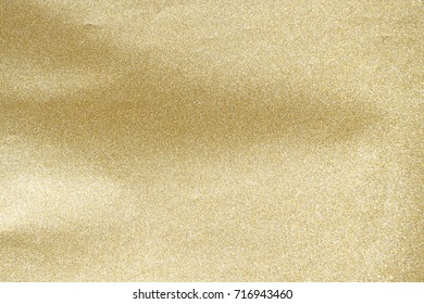 Paper wrapped gold foil paper, shiny, sparkling background for decorative elements.