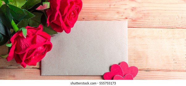 Paper for your text and small red hearts, rose on old wood background. Valentine gift.