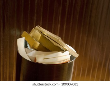 paperback books piled in trash can