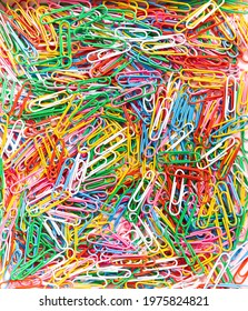 Paperclips colourful rainbow wallpaper. Festive party background made of paper clips for office supplies store