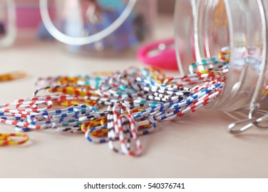Paperclips in glass jar on wooden table, close up
