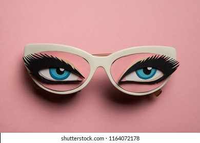 Papercraft eyes with eyelashes and sunglasses on blue backround.