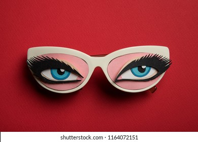 Papercraft eyes with glasses on red backround.