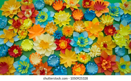 Papercraft flowers on green background, top view, flat lay. Decoration. Concept.