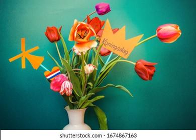 A paper-cut crown with the words Koningsdag stands in a vase with tulips. Koningsdag or King's Day is a national holiday in the Kingdom of the Netherlands.